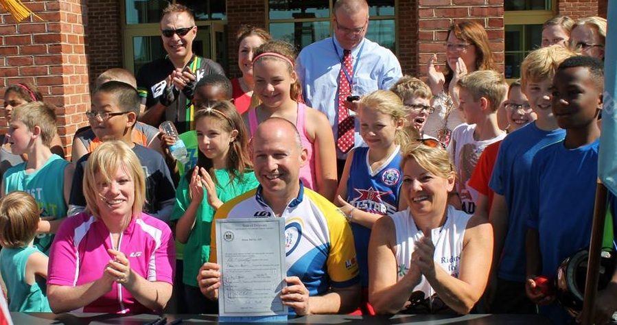 Governor Jack Markell (center) shows off the bill making cycling the Official Sport of Delaware while bill sponsors Senator Nicole Poore (left) and Representative Valerie Longhurst (right) and kids from Wilbur and Southern Elementary Schools applaud.
